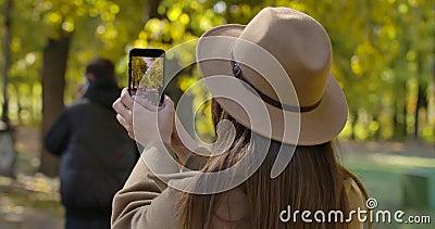 Rückansicht des jungen kaukasischen Mädchens in Braun, der Fotos des Herbstparks auf ihrem Smartphone macht Angenehmer europäisch stock video footage