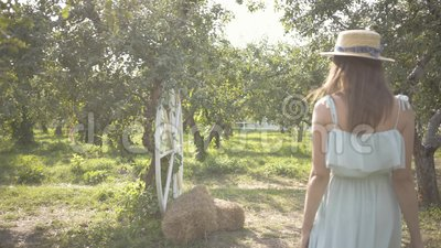 Rückansicht einer bezaubernden jungen Frau mit Strohhut und langem weißem Kleid durch den grünen Sommergarten. sorglos stock video