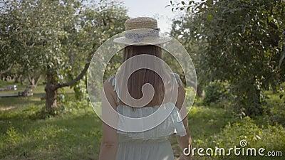 Rückblick auf attraktive junge Frau mit Strohhut und langem weißes Kleid, das durch den grünen Sommergarten geht. sorglos stock footage