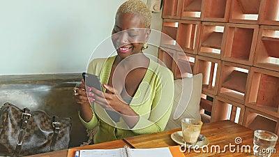 Ręczny strzał atrakcyjna i szczęśliwa czarna afro Amerykańska biznesowa kobieta pracuje online z telefonem komórkowym bierze nota zbiory