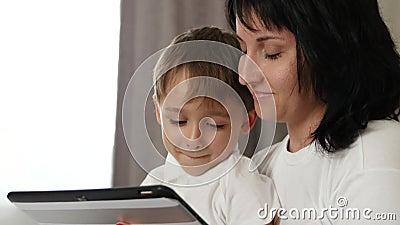 r Мать и ребенок смотря экран планшета с эмоциями: утеха, счастье, потеха сток-видео