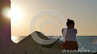 R?ver la jeune femme s'asseyant sur les roches pr?s de la mer au coucher du soleil banque de vidéos