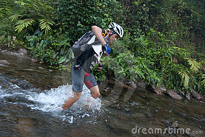 A racermakes his way across a river in the morning Editorial Image