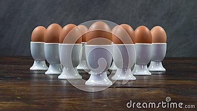 Rackfokus einer Gruppe gekochter Eier in weißen Ei-Bechern auf einem Holzküchentisch stock video