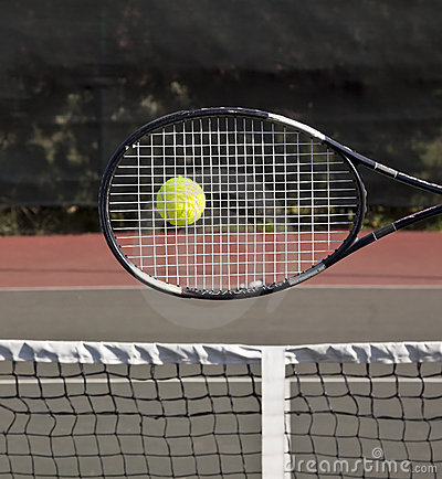 Racquet with tennis ball on court