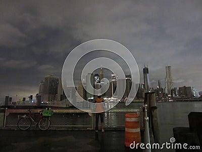 Radfahrer und dunkles Manhattan Redaktionelles Foto