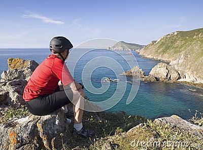 Radfahrersitzen, starrend entlang einer Küstenlandschaft an