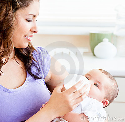 Radiant mother feeding her adorable son at home