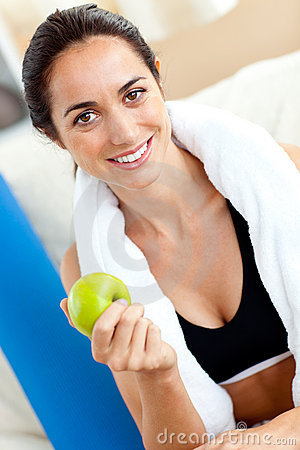 Radiant woman eating an apple after working out