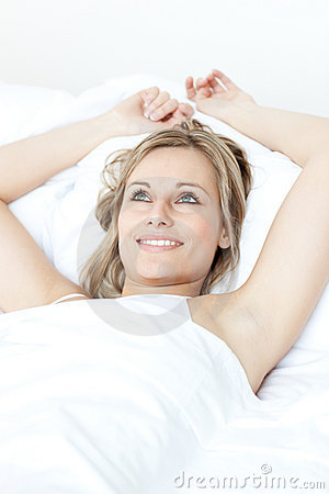 Radiant woman relaxing  lying on a bed