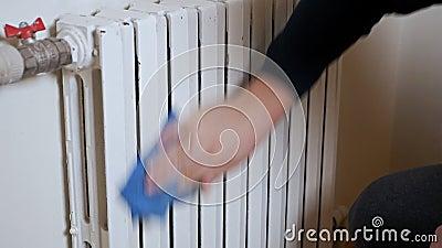 Radiateur sur un mur Une main masculine nettoie un radiateur chauffant Froid, hiver, chauffage, maison banque de vidéos