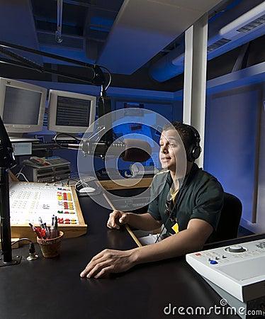 Radio DJ announces news in a studio