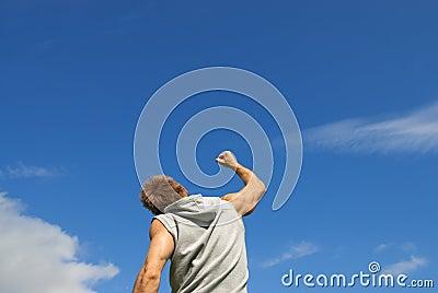 Radość młody człowiek z jego ręką podnoszącą w radości