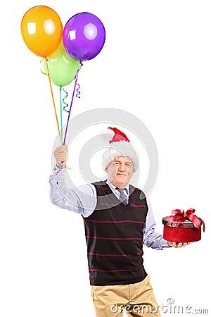 Radosny dżentelmenu mienia prezent i balony