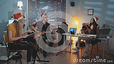 Radosny zespół muzyczny w Santa kapelusze śpiewające piosenki bożonarodzeniowe i grające instrumenty zdjęcie wideo