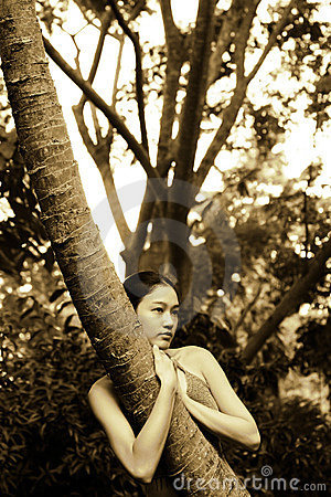 Ragazza asiatica che abbraccia albero