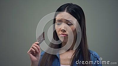 Ragazza asiatica triste che sogna del cioccolato zuccherato che tiene dieta, nutrizione sana stock footage
