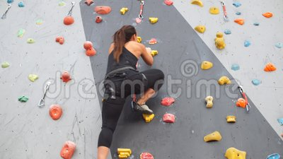 Ragazza atletica abbastanza giovane che scala su una parete dell'interno di scalata stock footage