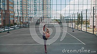Ragazza atletica in piedi su una gamba nella spaccatura Stretaggio e flessibilità Formazione sull'idoneità archivi video