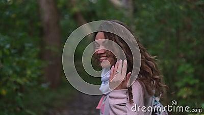 Ragazza che cammina nella foresta chiamandola per seguire la sua mano d'onda video d archivio