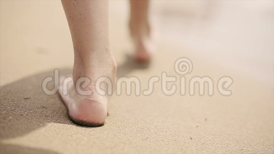 Ragazza che cammina a piedi nudi sulla sabbia della spiaggia lungo il mare Movimento lento