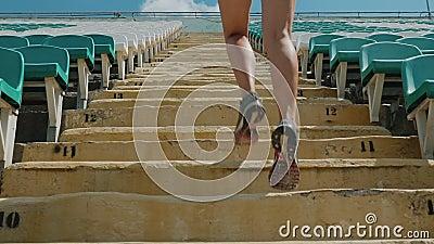 Ragazza che corre di sopra ad uno stadio Primo piano stock footage