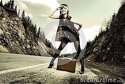 Ragazza che fa auto-stop con la valigia
