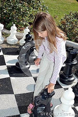 Ragazza che gioca il grande insieme di scacchi