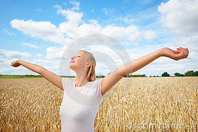 Ragazza che si leva in piedi in un campo del raccolto con le sue braccia alzate