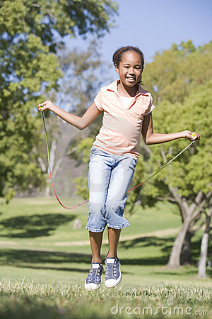 Ragazza che usando la corda di salto all aperto che sorride