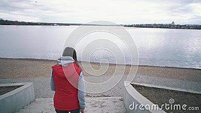 Ragazza con una giacca rossa senza maniche lungo i gradini fino al lago nel giorno nuvoloso stock footage