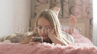 Ragazza curiosa che usa app telefoniche per guardare il dispositivo del cellulare seduto sul letto, bambino e gadget archivi video