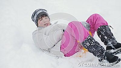 Ragazza del bambino che scende una slitta su una collina nevosa stock footage