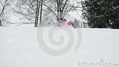 Ragazza del bambino che scende una slitta su una collina nevosa video d archivio