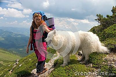 Ragazza del viaggiatore con zaino e sacco a pelo con il cane