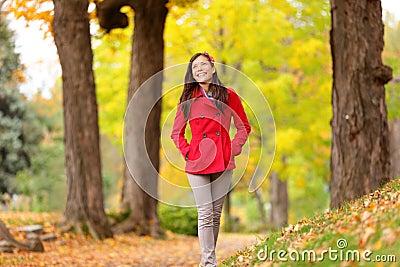 Ragazza di caduta che cammina sul sentiero nel bosco di autunno felice