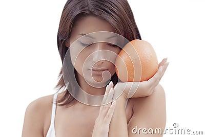 Ragazza di distensione con una frutta arancione