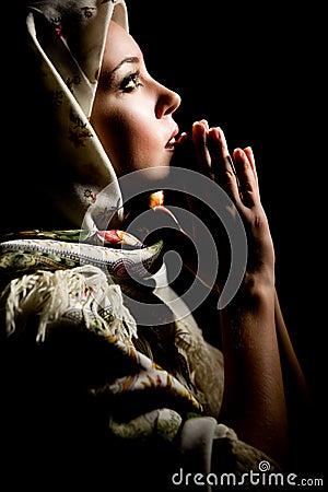 Ragazza di preghiera con lo scialle sulla testa. Retouched