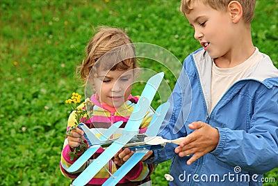 Ragazza e ragazzo con l aeroplano del giocattolo in mani