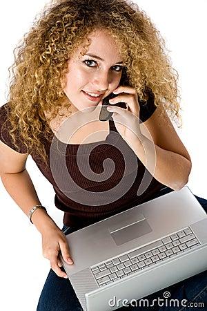 Ragazza sul computer portatile e sul telefono