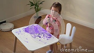 Ragazza Toddler dipinge un tavolo bianco con vernice viola Disordine creativo infantile Abitazione video d archivio