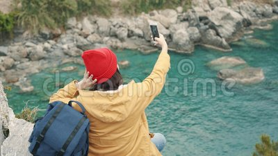 Ragazza turistica che si siede sull'orlo di una scogliera nella laguna e nel selfie di fucilazione stock footage