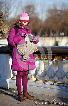Ragazza turistica felice con il sacchetto divertente e programma a Parigi