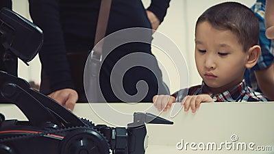 Ragazzo asiatico che guarda il robot sulla tavola alla mostra stock footage