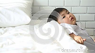 ragazzo asiatico che si rilassa accanto al letto dopo essersi svegliato al mattino in camera da letto Stili di vita delle persone video d archivio