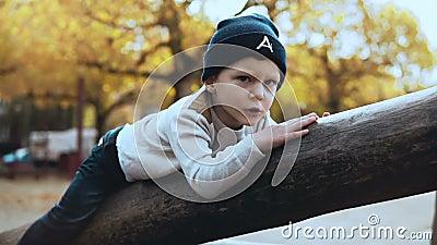Ragazzo caucasico prescolare divertendosi sul campo da giuoco Il bambino nervoso confuso in cappello ha attaccato sull'alto ostac archivi video