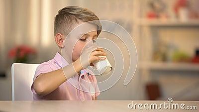 Ragazzo che beve latte organico fresco da vetro sulla tavola, alimento di energia di mattina, latteria video d archivio