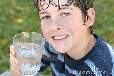 Ragazzo che beve un vetro di acqua