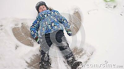 Ragazzo che fa un angelo sulla neve archivi video