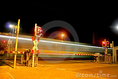 Railroad crossing at night with a Metro